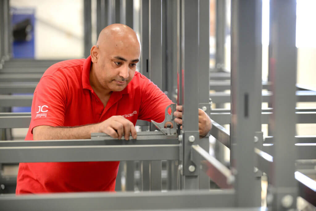 man checking for the precision manufacture and assembly of a metal stand